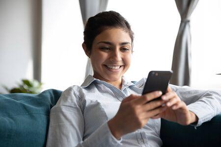 Lächelnder indischer Mädchenbenutzer, der ein Smartphone hält, schaut sich das Handy mit der mobilen Social-Media-App an