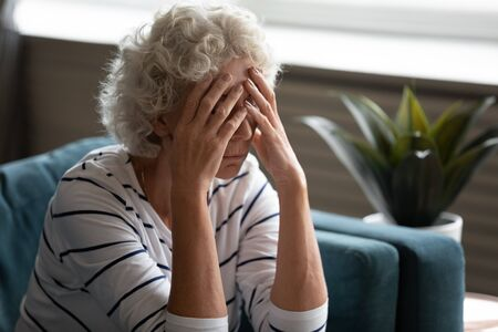 Close up 70s elderly woman sitting on sofa feels desperate crying covered face with hands, senile sickness need help, mental disorder or dementia, does not see way out difficult life situation concept