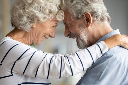 Close up profile faces 65s spouses loving couple sweet moment of tenderness, wife put hands on husband shoulders touching with foreheads laughing enjoy life together, old people eternal love concept Stock Photo - 137224620