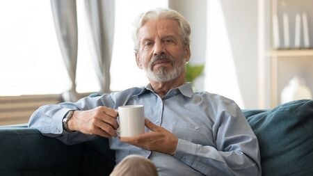 Confident 60s elderly grey-haired man sit on couch holding coffee cup looking at camera, bearded hoary grandfather spend time at home relaxing feels carefree, enjoy morning tea, photo shooting indoors