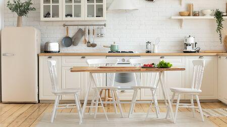 Moderne gezellige binnenlandse keuken interieur, op eettafel verse groenten huiseigenaren geven de voorkeur aan gezond eten, lening hypotheek nieuwe studio te huur, inrichting advertentie, renovatie diensten concept Stockfoto