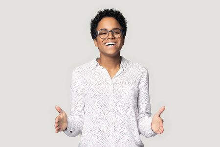 African young woman pose isolated on gray background smiling looking at camera stretched hands showing something big or large feels satisfied
