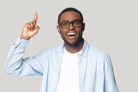 African guy raised index finger up came up with great cool fresh business idea feels happy looking at camera isolated on gray background