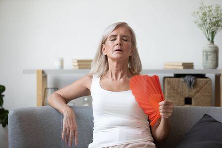 Chora starsza emerytka siedzi na kanapie, czuje się odwodniona, zmęczona upałem, używa machania ręką, aby się ochłodzić