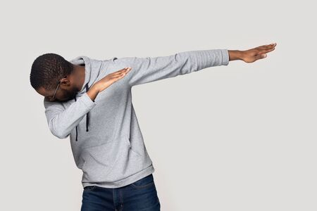 African guy makes dab, perform dabbing dance move point one arm towards aside while bowing head into other hand isolated on grey copy space wall