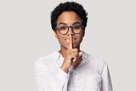 Studio head shot portrait attractive mixed-race african girl in glasses hold finger on lips showing gesture of silence look at camera pose isolated on grey background