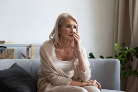 Pensive senior woman grandmother sit on couch look in distance thinking or remembering Standard-Bild