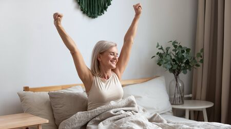Active happy mature female wake up from good healthy sleep stretching sitting in bed at home