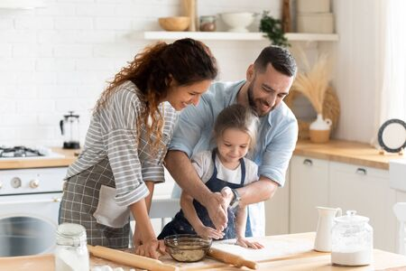 Small adorable kid girl preparing pie with loving caring parents on domestic kitchen, young family enjoy cooking process at home Stock Photo - 136964637