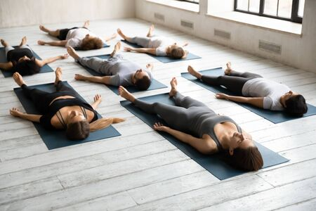 Diverse sporty young people practicing yoga at group lesson, relaxing in Savasana exercise on mats, meditating in Corpse pose on floor, training, working out in modern yoga studio, center