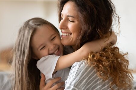 Close up beautiful young mother snuggle little cheerful daughter laughing enjoy moment of tenderness having fun spend time together at home, next generation and offspring, unconditional love concept