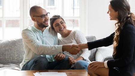 Smiling multiethnic millennial couple handshake positive female realtor or broker get acquainted at meeting