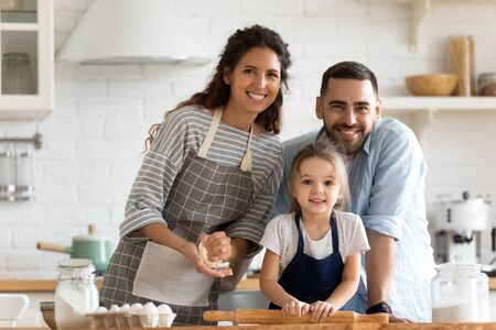 Couple and her little adorable daughter preparing pastries together on domestic modern kitchen posing smiling looking at camera, concept of family portrait, happy parenthood, help and cooking at home Stock Photo - 137027176