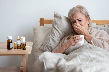 Sick old woman lying in bed at home feel sick suffer from flu or cold cure with prescribed medications, unhappy senior female struggle with illness alone at home, elderly healthcare, solitude concept