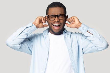 African guy having discontent look plugging his ears being annoyed with noisy neighbours or alarm wanting silence and calm feels exhausted of loud sound and shouting posing isolated on gray background