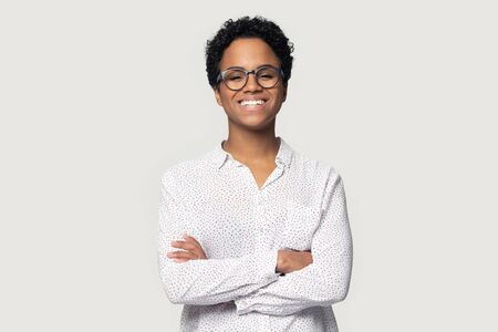 Attractive African ethnicity woman wears casual blouse and glasses pose isolated on gray background standing with arms crossed having wide beautiful smile looks at camera feels confident and healthy