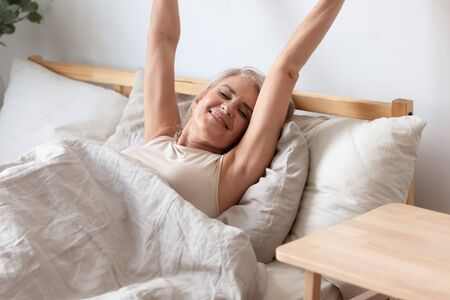 Happy positive senior woman stretching in bed wake up in good mood welcoming new sunny day, smiling optimistic mature female awaken after healthy sleep in comfortable bedroom at home