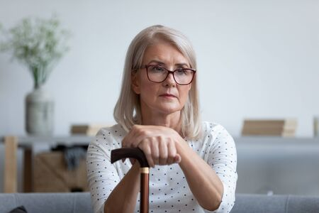 Sad elderly woman grandmother in glasses sit hold lean on wooden cane look in distance thinking remembering, upset senior female retiree use walking stick feel lonely abandoned, solitude concept