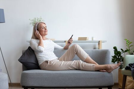 Calm mature woman relax on cozy couch at home wear earphones enjoy music using modern cellphone, modern senior female gadget user in headphones listen to favorite track good sound on smartphone