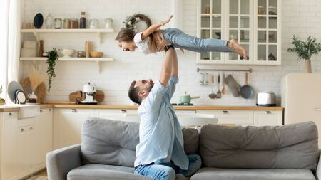 Happy funny little kid girl flying in fathers arms family having fun in modern studio apartments, loving single daddy holding lifting cheerful pre-school daughter playing plane enjoy playtime at home Stock Photo - 136935835