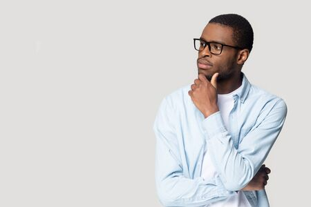 African concerned guy isolated on gray background touch chin feels doubting, bespectacled man look aside at copy space thinking about vision correction clinic procedure, choose make decision concept Stock Photo