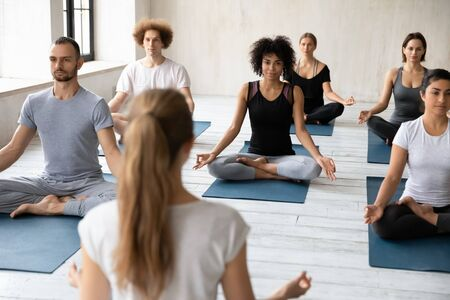 Female instructor training diverse young people at group lesson rear view, practicing yoga, doing Padmasana exercise, sitting in Lotus pose on mats, working out, meditating in modern fitness center