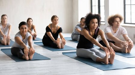 Diverse people with African American female instructor doing Seated forward bend exercise, practicing yoga at group lesson, stretching in paschimottanasana pose, working out in modern yoga center
