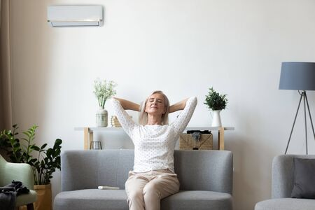 Calm middle-aged retired female sit rest on cozy sofa breathe fresh air in condition living room