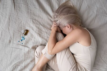 Top view of unhappy senior woman lying in bed with bottle of medicines or pills struggle with depression, upset depressed mature female suffer from insomnia or psychological problems, overdose concept