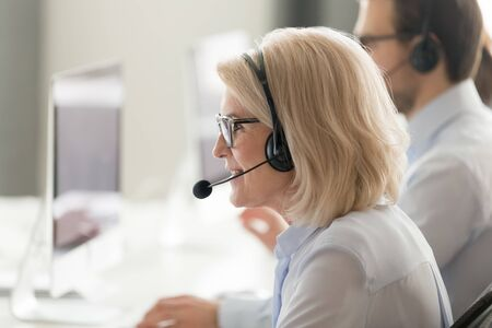 Close up of middle-aged woman call center agent wearing headset speak consult client online at helpdesk, senior female operator work at helpline in customer service shared office using computer