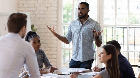Los colegas masculinos multiétnicos locos pelean en una reunión de la empresa en la sala de juntas de la oficina, los compañeros de trabajo de diversos hombres que tienen malentendidos se sienten furiosos y enojados, disputan en la sesión informativa corporativa