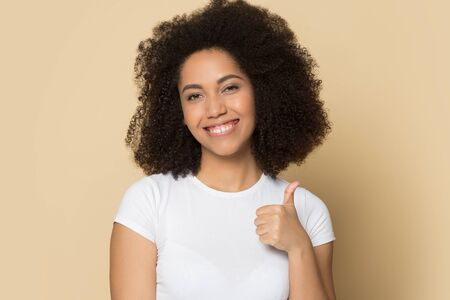 Head shot close up studio portrait young african american lady showing like, thumbs up gesture. Satisfied female customer evaluating positively product or service isolated on yellow background,