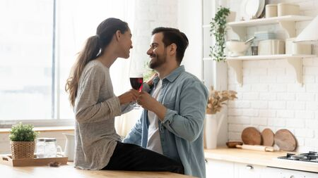 Cheerful young mixed race woman sitting on wooden countertop, holding glass of red wine, chatting with husband. Happy married couple celebrating special event or enjoying romantic time together. Banque d'images
