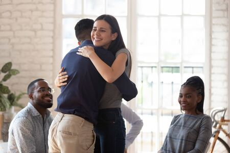 Smiling young man and woman hug show love and care involved in psychological therapy session in studio, happy diverse people embrace feel supportive to friend at counseling addiction treatment