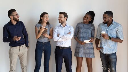 Happy successful multiethnic millennial employees stand in row talk laugh in office hall, smiling young diverse multiracial young people or colleagues gather near white wall show unity and team spirit