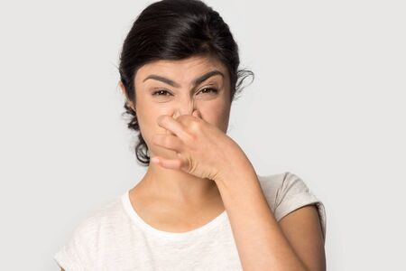 Disparo a la cabeza de cerca retrato infeliz joven india cerrando la nariz, conteniendo la respiración, sufriendo de un olor desagradable intolerable, evitando un olor fuerte desagradable aislado sobre fondo gris de estudio. Foto de archivo
