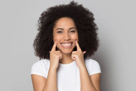 Funny african american young lady extending smile by hands head shot close up portrait. Satisfied female client demonstrating teeth whitening procedure excellent result isolated on gray background. Stock Photo