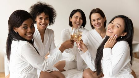 Portrait of smiling multiracial female friends in bathrobes have fun cheers drink champagne enjoy hen party, happy diverse millennial girls celebrate bachelorette bridal shower in bedroom together