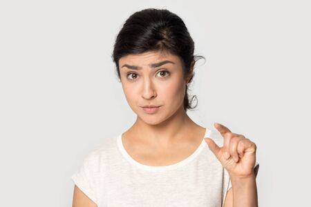 Confused upset millennial indian ethnicity girl looking at camera, showing small size, demonstrating little measurement, dissatisfied with small product discount isolated on grey studio background. Imagens