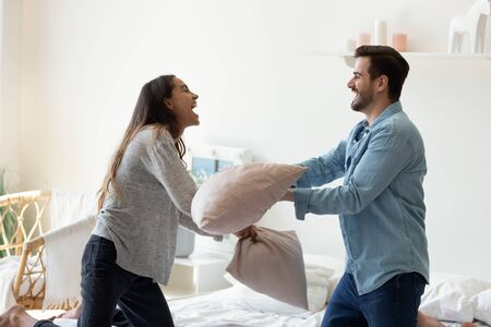 Overjoyed funny young married spouse fighting with pillows in bedroom. Happy playful mixed race family couple laughing, having fun, enjoying active weekend time together at home or hotel room. Stock Photo