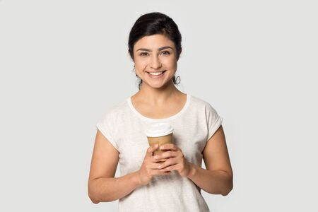 Head shot portrait millennial happy smiling indian ethnicity lady holding take away paper craft hot coffee tea cup, warming herself at morning, having break pause isolated on grey studio background. Stock Photo
