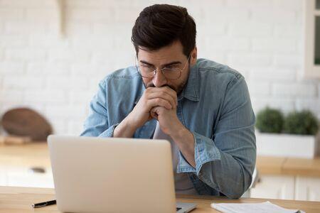 Disparo a la cabeza empresario pensativo en gafas mirando la pantalla del ordenador, sentado a la mesa en casa. Pensativo joven confundido pensando en la solución del problema atascado con la tarea, trabajando con la computadora portátil de forma remota.