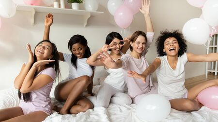 Portrait of overjoyed multiracial millennial girls in pajamas look at camera smile pose at home bridal shower, happy diverse female friends laugh have fun celebrate bachelorette hen party together