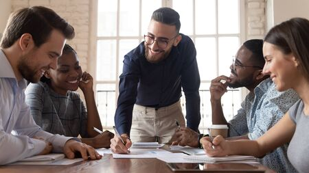 Smiling Arabian millennial businessman hold meeting with multiethnic colleagues explain financial paperwork at briefing, successful young Arabic male ceo or boss lead team briefing in office