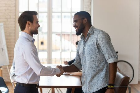 Smiling male Caucasian boss or director shake hands of excited african American employee greeting with work promotion, happy business partners handshake closing deal at office, cooperation concept