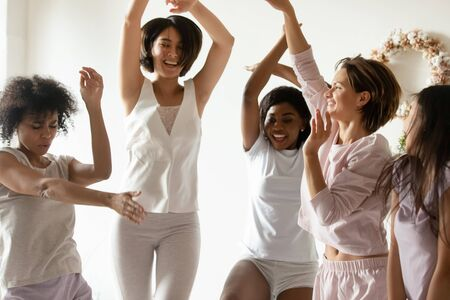 Excited multiracial female friends wear pajamas smile laugh celebrate bachelorette bridal shower together, happy overjoyed multiethnic diverse millennial girls dance have fun enjoy hen party at home Stock fotó