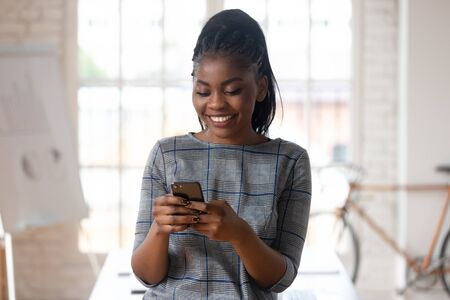 Close up of happy biracial millennial female employee using modern cellular texting messaging via wireless internet connection, smiling african American businesswoman browsing smartphone in office