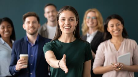 Friendly young company woman representative holds out her hand for handshake welcoming customer smiling looking at camera posing together with diverse colleagues, sales manager greeting client concept Stock Photo