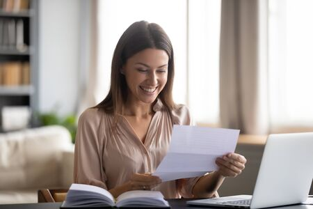 Smiling young woman sit at desk working feel overjoyed reading good news in paper post letter, happy millennial girl distracted from studying get great message in postal correspondence or notice