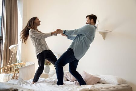 Full length overjoyed young family couple dancing to favorite music on cozy bed together at home or hotel. Happy mixed race spouse having fun in bedroom, enjoying crazy weekend vacation active time. Stock Photo